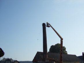 Shazování starého hnízda z továrního komína.