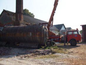 Cisterna pod továrním komínem, vpravo vysokozdvižná plošina.