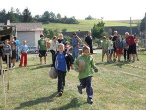 Děti běžící s hadicemi.