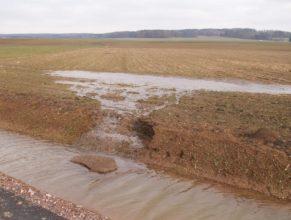 Voda tekoucí z pole do příkopu.
