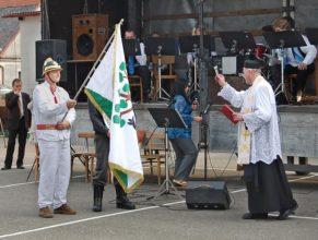 Kněz žehnající znaku a vlajce obce.
