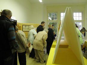 Návštěvníci prohlížející si fotografie obce.