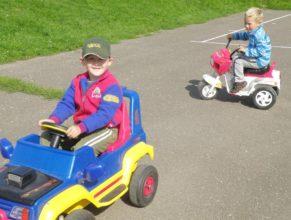 Děti vozící se v autíčku a motorce.