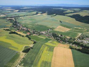 Pohled na Vlčkovice, vlevo Dolní Vlčkovice, vpravo Vlčkovice Horní. V pozadí nalevo Dvůr Králové nad Labem a napravo pak pohoří Krkonoše.