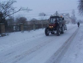 Přijíždějící traktor se sněhovým pluhem u obecního úřadu.