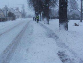 Dobrovolní hasiči odklízející sníh z chodníku u obecního úřadu.