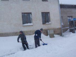 Dobrovolní hasiči odklízející sníh z chodníku před bývalou budovou JZD.