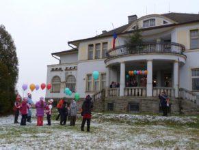 Děti s balónky před obecním úřadem.
