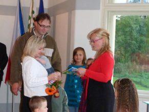 Eva Bittnerová předávající květinu a dárek manželům Kosinkovým, Ivaně a Miroslavovi, se synem Jakubem narozeným 3.6.2011.