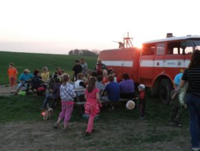 Posezení na kopci před vatru připravenou na čarodějnice. V pozadí hasičské vozidlo místního sboru dobrovolných hasičů.