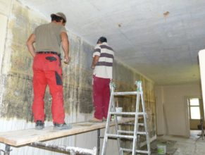 První patro obecního úřadu, dělníci odkrývající malby na zdech.