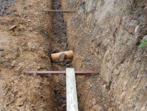Stavba hriště - základy, oranžová trubka chránící starý přívod vody.