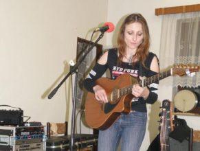 Zpěvačka hrající na kytaru.