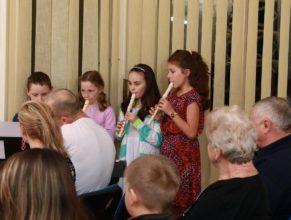 Děti hrající na flétny a na piáno.
