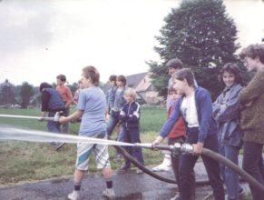Děti zkoušející hasící techniku na dětském dnu.