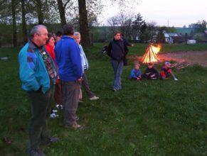 Obecenstvo, v pozadí oheň na opékání buřtů.