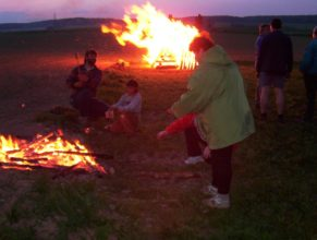 Opékání buřtů, v pozadí hořící vatra čarodějnic.
