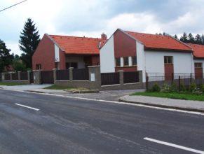 Nově postavené budovy na místě bývalé školy vedle kostela.