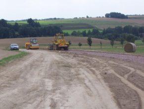 Výstavba cesty C 2.5 HV od lesa Bokouš. Pohled na Horní Vlčkovice a pracovní stroje.