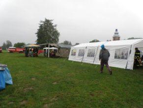 Návštěvníci a družstva skrývající se pod stany před deštěm.