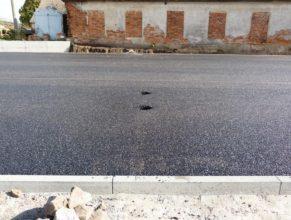Nově položený asfalt na hřišti, díry pro kůly.