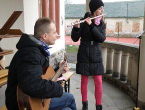 Dívka hrající na flétnu s doprovodem kytaristy.