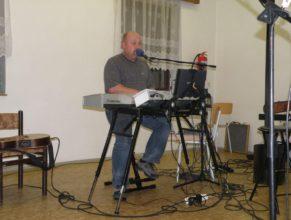 Zpěvák hrající na klávesy.