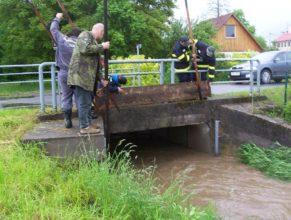 Hasiči zvedající hráz na mostě u Trohořů v Horních Vlčkovicích.
