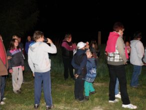 Rodiče s dětmi sledující hořící hranici čadodějnic.